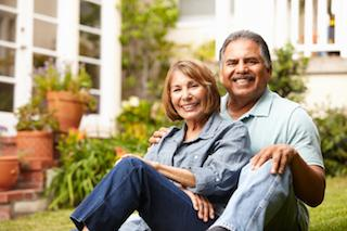 a couple sits happily in their garden | Dental Implants Candia NH
