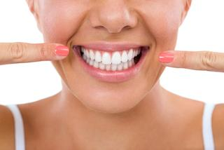 a woman points to her smile | candia nh preventive dentist