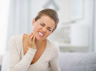 a woman holds her jaw in pain | tmj treatment Candia NH