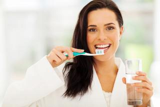 a woman holds a glass and a toothbrush | Preventive dentist candia NH